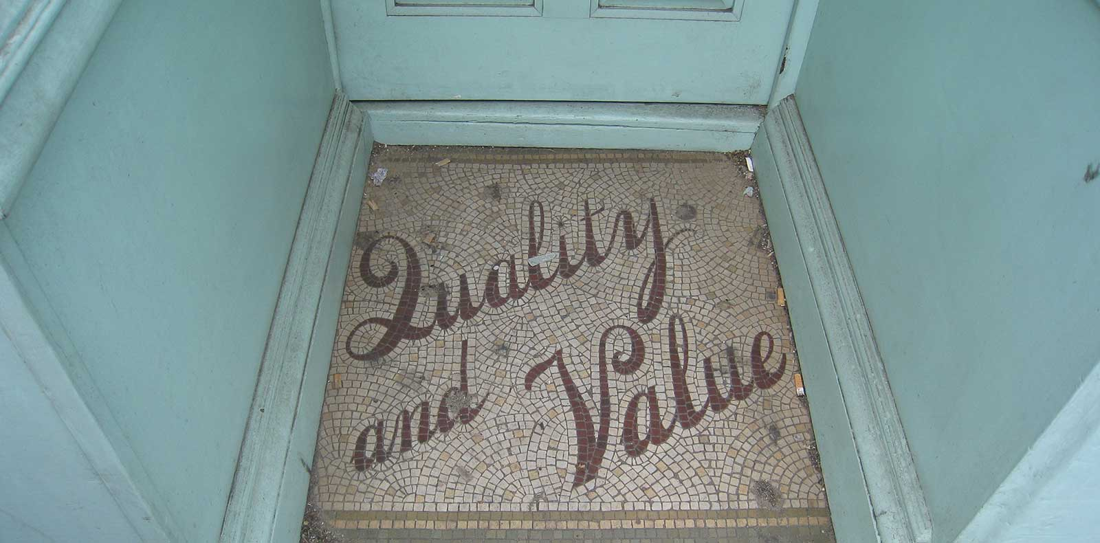 "Old tiled doorway with mosaic saying, ""Quality & Value"""